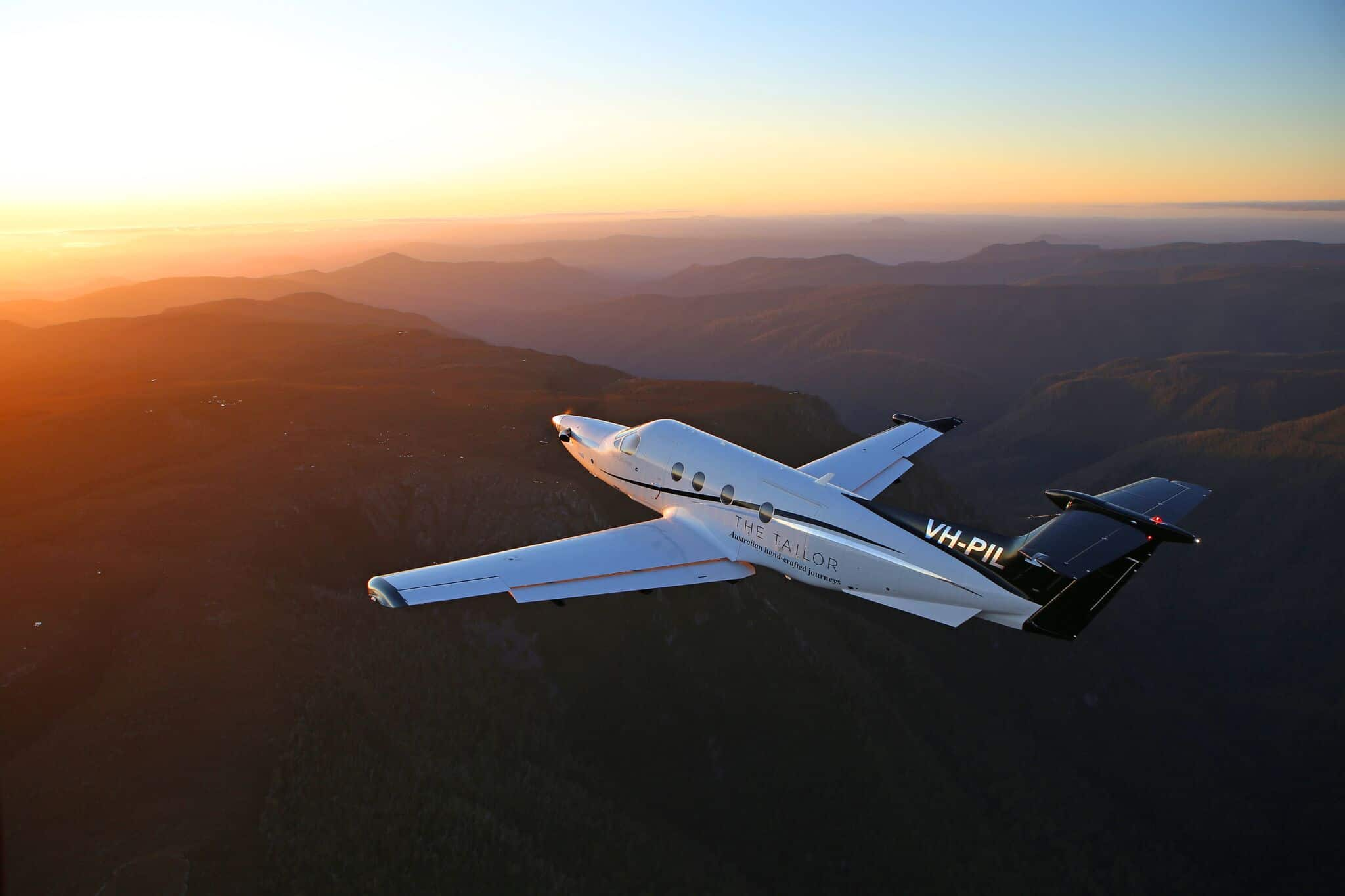 A Pilatus PC12 Fly's high above the mountains off into the sunset