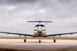 A Pilatus PC-12 sits on a runway with gray clouds surrounding it, blue card membership